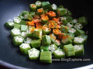 adding spices to okras for dahi bhindi recipe