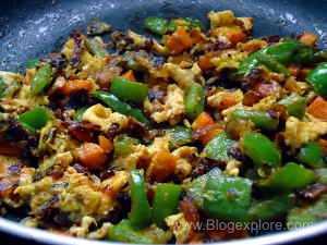 stir frying veggies and eggs for egg fried rice