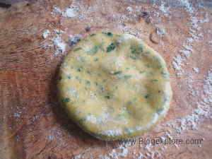 dusting the dough disc with flour for drumstick leaves paratha