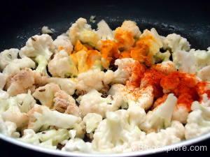 adding spices to make gobi matar