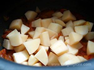 adding potatoes for aloo tamatar sabzi